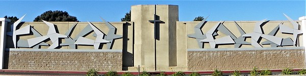 Seagulls flying toward the cross.