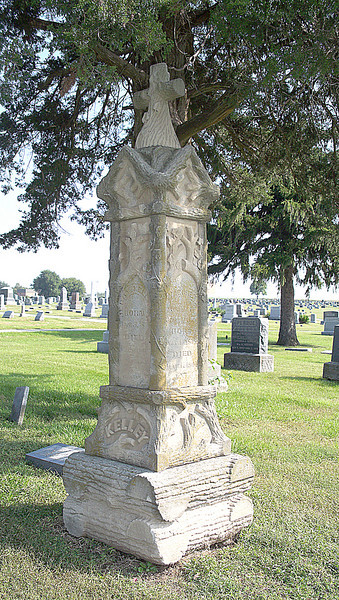 Similar in nature to the other tombstone with wood branches carved on the stone except this is topped with a cross.  Growing trees symbolize life but parts of trees or tree limbs often indicate life cut short. The cross is a symbol of Christianity, faith and resurrecton.  Note that the cross is made to look like it is carved from wood.  The base of the tombstone is similar to the other one in that it is stone resembling logs. City Cemetery, Higginsville, Missouri.  Sept. 21, 2008