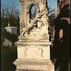 The Bales stone has the broken, leaning tree trunk indicating interrupted life, and mourning.  The hour glass in the upper region of the stone indicates swift passage of time, temperance and the inevitablity of death.  Elmwood Cemetery, Kansas City, Missouri Dec. 9, 2001