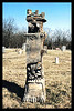An example of W.O.W. tombstone provided for members of the Woodmen of the World orginazation.  Symbols of their work are seen on the top of the tree trunk.  Hillcrest Cemetery, Gallatin, MO.  April 3, 2002.  (Scanned from photograph)