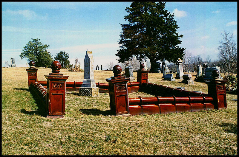 A family plot is  surrounded by an unusual brown ceramic wall and posts.  Only one I've ever seen.  Miami, Saline Co., Missouri.  Highway 41.