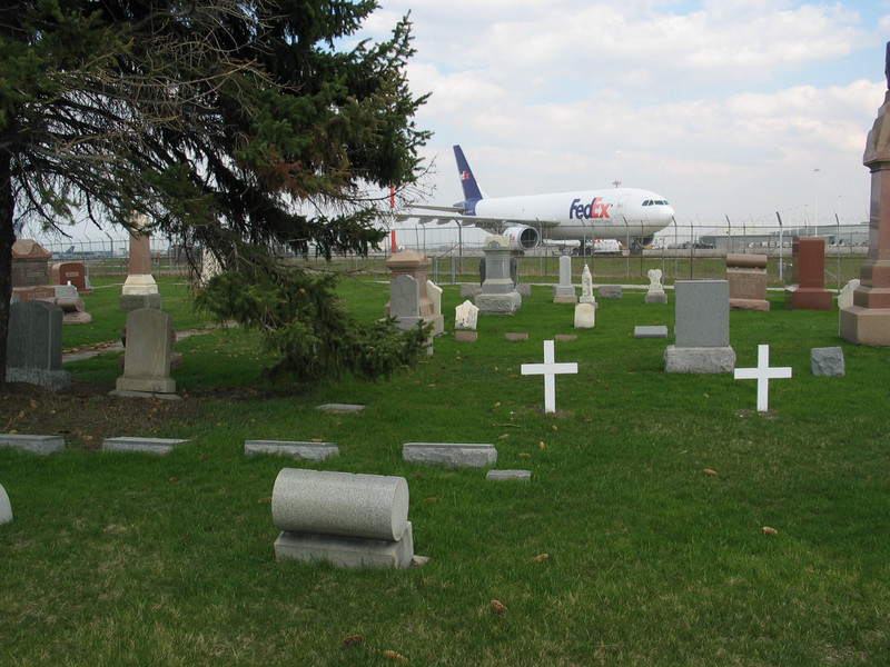 FedEx airplane behind cemetery