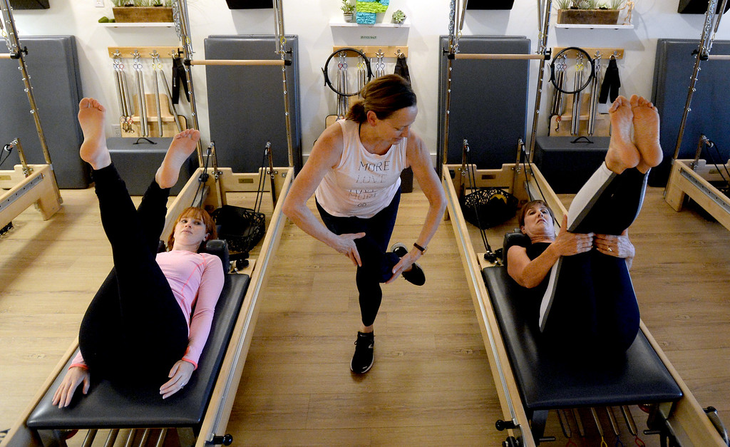 . LOUISVILLE, CO: November 6: Instructor, Tracy Bodder, center, works with Emily Pancoast, left, and Dawn Lotan on Tuesday. Center Stream Pilates, in Louisville, is the Workout of Week. (Photo by Cliff Grassmick/Staff Photographer)