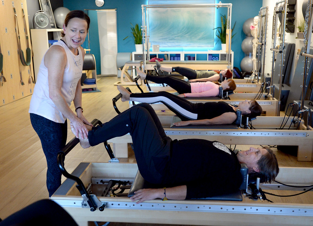 . LOUISVILLE, CO: November 6: Instructor, Tracy Bodder, helps Danny Parizek with his form. Center Stream Pilates, in Louisville, is the Workout of Week. (Photo by Cliff Grassmick/Staff Photographer)