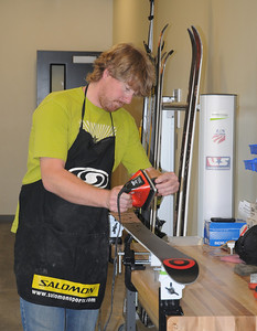 Ski Technician Chris Taylor waxes a pair of skis in the tuning room at the USSA Center of Excellence in Park City, Utah.