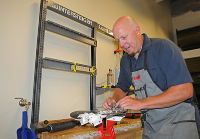 U.S. Snowboarding technician Andy Buckley scrapes a competition board in the tuning room of the USSA Center of Excellence.