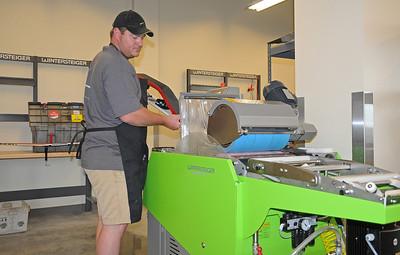 Wintersteiger technician Ryan Eittreim sends a ski through the grinder in the USSA Center of Excellence tuning room.