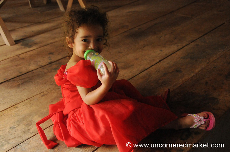 Little Girl in Red with a Feeding Bottle - Perquin, El Salvador