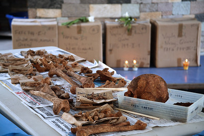 Guatemala. Forensic teams lay out the exhumed remains unearthed from a mass grave. The boxes in the background contain bones, as well as retrieved personal items such as jewelry, clothing and/or shoes that, along with DNA testing, is helpful in identifying the victim(s). (Panetta)