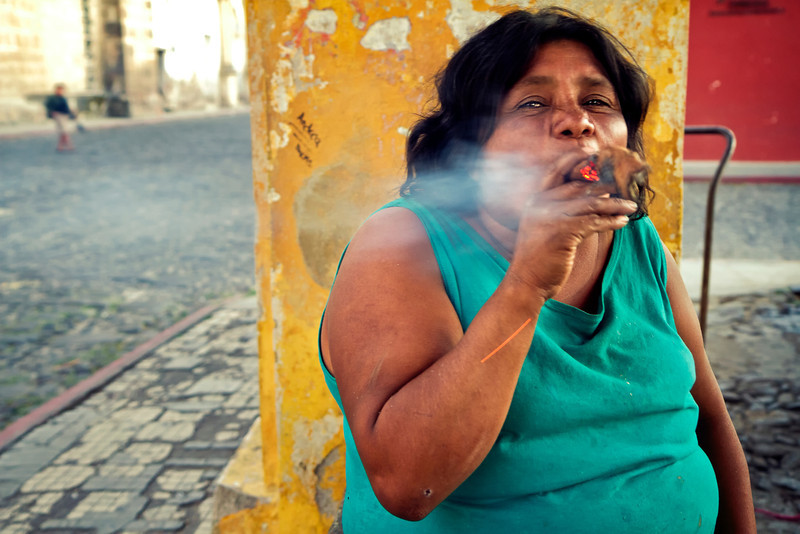 Local woman smokes a giant cigar as she washes clothes.