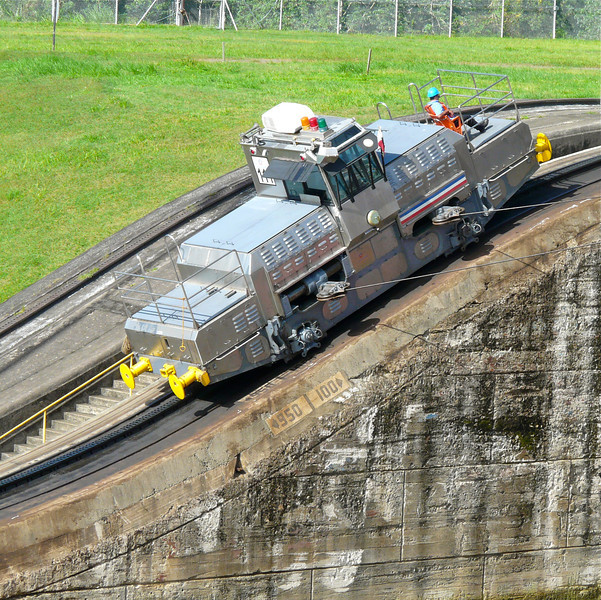 A train is attached to a ship in the Panama Canal
