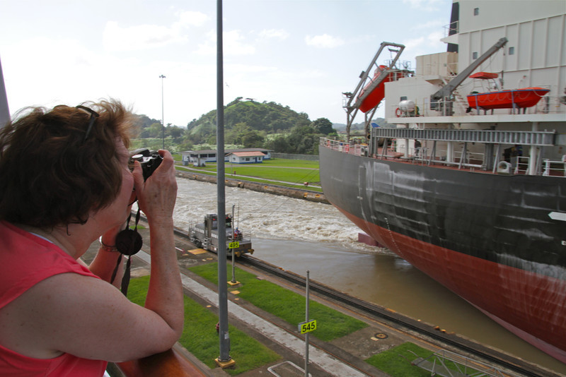 Woman photographs a ship in the Panama Canal