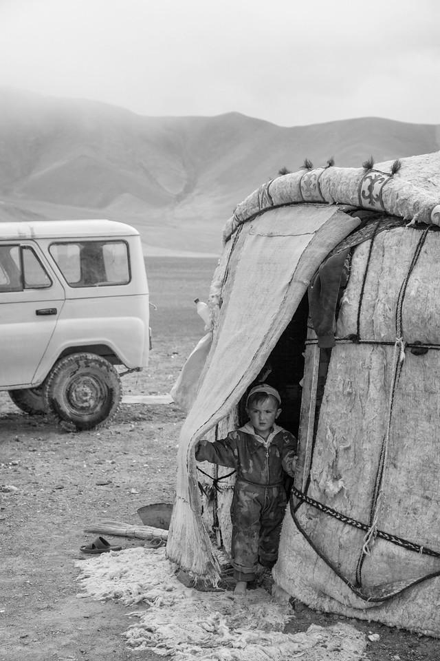 Boy peers out of a yurt, East of Rang Kul