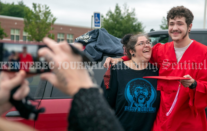 AUGUSTA, ME - JUNE 25: Kristi Moreau, left, laughs as she poses for a photo with her son Kaleb Coron before Augusta adult education graduation Friday June 25, 2021 outside Cony High and Middle School in Augusta. (Staff photo by Joe Phelan/Staff Photographer)