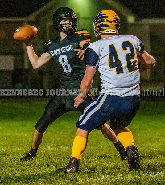 READFIELD, ME - OCTOBER 1: Maranacook's Chris Reid passes under pressure from Boothbay's Kayden Ames <br /> during a football game Friday October 1, 2021 at the Ricky Gibson Field of Dreams in Readfield. (Staff photo by Joe Phelan/Staff Photographer)