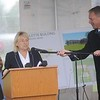 Gov. Janet Mills and David Pelton, director of real estate development for Kennebec Valley Community Action Program, share a light moment Tuesday as Pelton adjusts the microphone during a ceremony to mark an affordable housing project in Skowhegan. House Speaker Ryan Fecteau is at left.  — Rich Abrahamson/Morning Sentinel