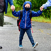 RICHMOND, ME - SEPTEMBER 2: Flanked by his parents, Eric Hunnewll, left, and Darlene Hunnewell, right, kindergartner Logan Hunnewell walks towards the door in the rain on the first day of the 2021-22 school year Thursday September 2, 2021 at Marcia Buker School in Richmond. Younger brother Rowan Hunnewell will be joining him there next week when pre-k classes start next week. It was the first student day for RSU 2 which includes Richmond, Dresden, Monmouth, Hallowell, and Farmingdale. (Staff photo by Joe Phelan/Staff Photographer)