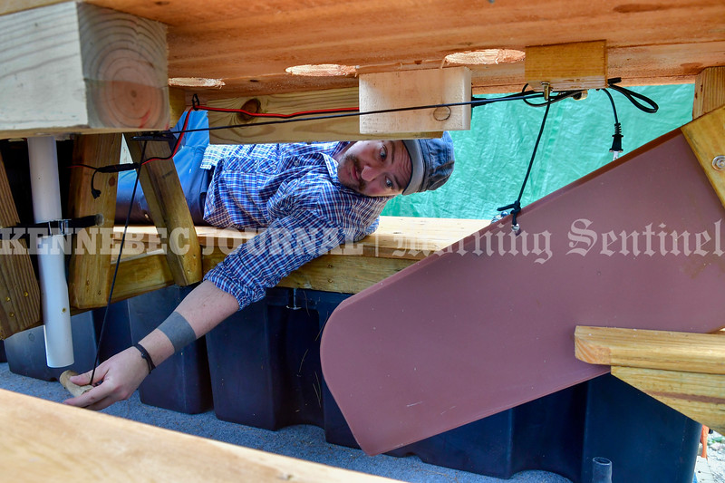 WINTHROP, ME - SEPTEMBER 1: Lon Cameron demonstrates the pulley system that pulls up the centerboard under one of picnic table watercrafts Wednesday September 1, 2021 on Wilson Pond in Winthrop. The wooden dowel fits into base of umbrella to hold it up when not in use. (Staff photo by Joe Phelan/Staff Photographer)