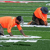 AUGUSTA, ME - OCTOBER 13:  Geo Surfaces workers cut out the green part under football yard line markers Wednesday October 13, 2021 on Cony High School's Fuller Field in Augusta. After carefully measuring and positioning the name, numbers and markings are nailed in place on top of the green and left to settle for a day. After that workers cut out the green part underneath and slide them in. (Staff photo by Andy Molloy/Staff Photographer)