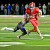 AUGUSTA, ME - OCTOBER 16: Cony quarterback Davyn Flynn  runs away from tackle attempt by Lawrence's Wyatt Poulin during football game Saturday October 16, 2021 on Cony's Fuller Field in Augusta. (Staff photo by Joe Phelan/Staff Photographer)