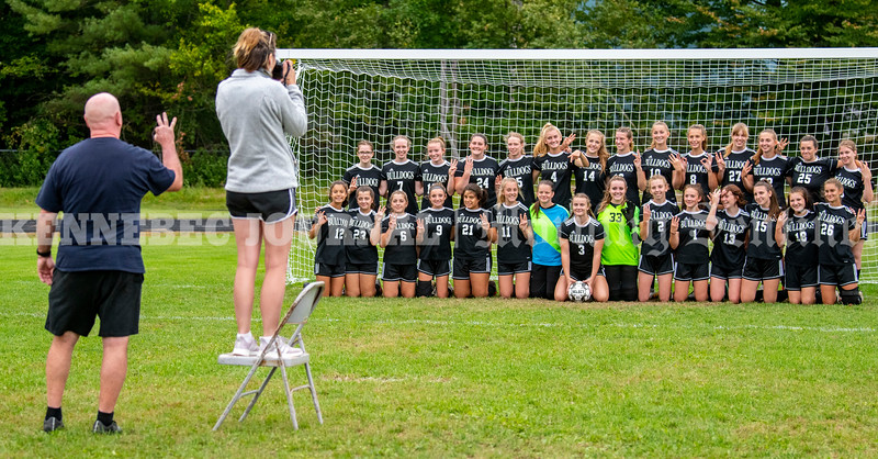 FARMINGDALE, ME - SEPTEMBER 22: Coach Guy Cousins, left, and assistant coach Sara O'Brien line players up for a team photo before practice Wednesday September 22, 2021 at Hall-Dale High School in Farmingdale. (Staff photo by Joe Phelan/Staff Photographer)