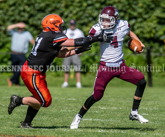 WINSLOW, ME - SEPTEMBER 18: Winslow defensive end Bailey Waldie, left, tries to tackle MCI quarterback Kyle Hall,  during a football game Saturday September 18, 2021 at Gerry Poulin Memorial Field in Winslow. (Staff photo by Joe Phelan/Staff Photographer)