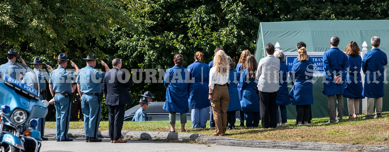 AUGUSTA, ME - SEPTEMBER 23: Office of the Chief Medical Examiner staffers, right, watch law enforcement personnel line for a ceremony transferring the body of Hancock County Deputy Luke Gross into their building Thursday September 23, 2021 in Augusta. Deputy Gross died after being struck by a vehicle earlier that morning and was brought to Augusta for a autopsy. (Staff photo by Joe Phelan/Staff Photographer)