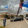 AUGUSTA, ME - SEPTEMBER 23: Augusta Fire Department personnel, top, and a Maine State Police Trooper salute as the hearse carrying the body of Hancock County Deputy Luke Gross drives beneath a large American flag Thursday September 23, 2021 as it turns off Hospital Street and into the Office of the Chief Medical Examiner in Augusta. (Staff photo by Joe Phelan/Staff Photographer)