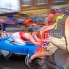 SKOWHEGAN, MAINE- AUGUST 5, 2021<br /> Mary Liz Taylor rides the bed as her teammates You Snooze You Lose during the annual bed races on Water Street in downtown Skowhegan as part of Main Street River Fest on Thursday, August 5, 2021. (Staff Photo by Michael G. Seamans/Staff Photographer)