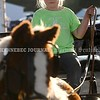 15243# 01fair SKOWHEGAN, MAINE AUGUST 15, 2021. Errie (cq) Mills, seven, holds the reins on a fake horse during the Skowhegan State Fair in Skowhegan, Maine Sunday August 15, 2021. Mills said she is showing horses at the fair. (Rich Abrahamson/Morning Sentinel)