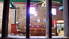 Java Junction Coffee Shop interior as viewed from a small side room looking through original wall studs.  You see the coffee roaster on the left and several of the purple windows above.  Beautiful hardwood flooring, tin ceilings and original brick walls add to the ambiance of this 1880's building.