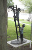 A bronze statue of a boy holding a ladder for his friend while he tries to rescue a cat in a tree.  Nancy Anderson Memorial Park, Warrensburg, Missouri.  In the background is another statue, this is a boy scrubbing puppies in a half-barrel tub.