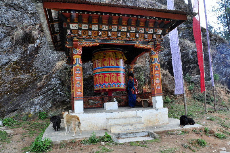 """This is a  medium sized village Prayer Wheel.  There are countless of these seems around the country of Bhutan, too. You'll find one in every village, town as well as by any monastery or temple. These are rotated manually by a person pushing a shaft and going in a circle clockwise. This is presumed to bring good luck to both the person pushing the Prayer Wheel drum as well as to those in the surrounding area. As with all Prayer Wheels, prayer verses are inscribed on the drum which are """"spun off"""" into the surrounding air to give blessing to the area. <br /> This one is near the airport in the Western town of Paro."""