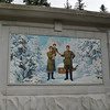Sign in Mt. Paekdu and Secret Camp area in north on border with China. Shows Kim il Sung and Kim Jong il as child with mother. Scene supports official storyline of Kim Jong il being born in North Korea in father's wartime HQ camp here in 1942. Mt Paekdu area, North Korea