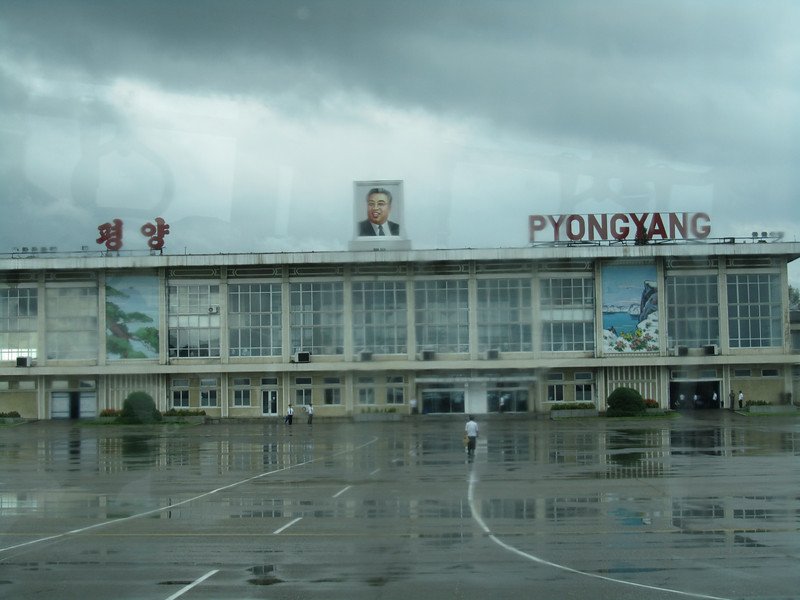 At Pyongyang airport. A portrait of a beaming Kim il Sung above the terminal greets the visitor. Pyongyang International Airport, North Korea