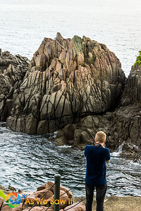 A photo of Chris Gee taking a photo of a rock.  The lines cut by never ending tidal changes create interesting patterns and contrast.