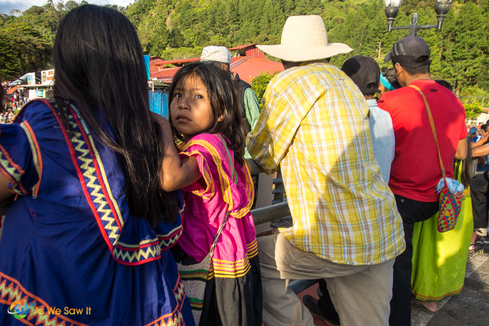 Little Embera girl with her mother looking over her shoulder at the rides she wants to enjoy