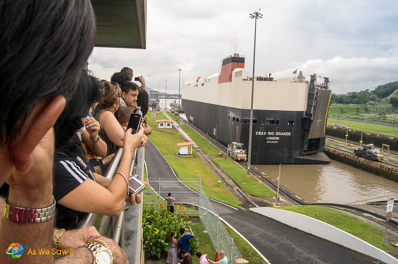Visitors on the Miraflores viewing platrorm watch a ship navigate a lock