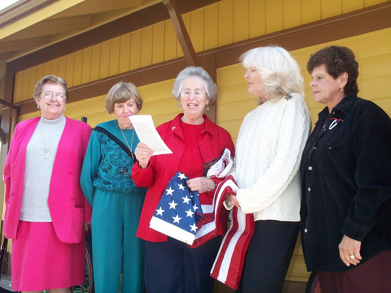 Museum Assistant Director Phyllis Olsen accepts the American Flag from Parlor President Dolores Hartnett.