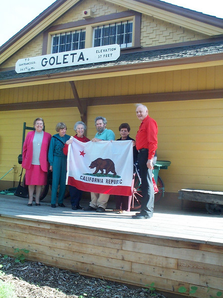 Museum Director Gary Coombs accepts the California Flag from Parlor President Dolores Hartnett.