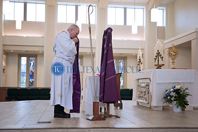 Bishop Edward J. Burns kisses his stole as he removes it in preparation to prostrate at the front of the altar during the Ceremony of Sorrows at St. Cecilia Catholic Church October 9.