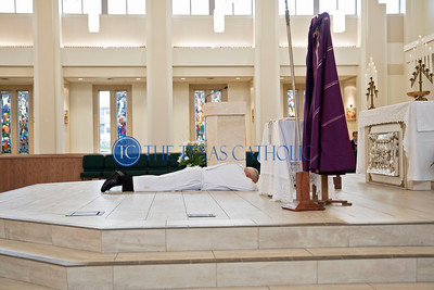 Bishop Edward J. Burns lays prostrate at the front of the altar during a Ceremony of Sorrows at St. Cecilia Catholic Church October 9.