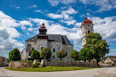 Jednoloďový kostol z cca prvej polovice 13. storočia s polkruhovou apsidou, pristavanou južnou vežou a severnou sakristiou.