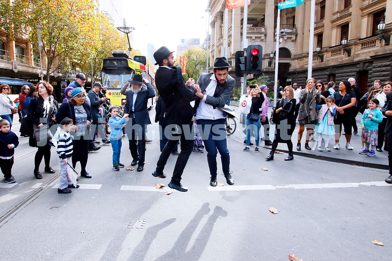 Jumping for joy. Celebrating a new torah for Chabad CBD, the parade takes over the corner of Collins and Swanston streets. Photo: Peter Haskin