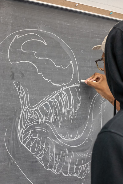 A K-State student draws a picture of Venom on a blackboard in Cardwell hall. (Jordan Koster|Collegian Media Group)