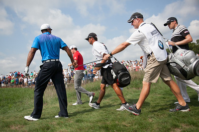 Tiger Woods hands his club to his caddy after hitting off the 10th tee during first round action at the BMW Championship at Crooked Stick CC in Carmel Indiana on Thursday Sept. 6, 2012. (Charles Cherney/WGA)