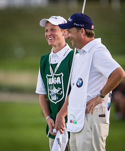 Evans Scholar Paul Stadem has a laugh with Rory Mciiroy's caddy J. P. Fitzgerald at the 17 green. Stadem is an honorary caddie at the BMW Championship in Carmel Indiana on Saturday Sept. 8, 2012. (Charles Cherney/WGA)