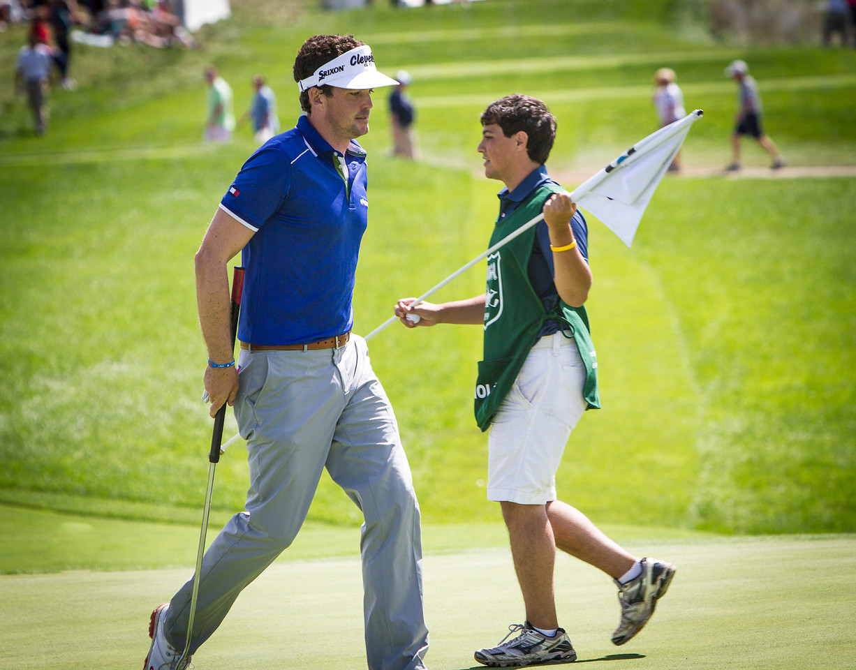 Evans Scholar Justin Cruz puts the pin back in the hole at 17 while player Keegan Bradley heads tot he 18th tee box at the BMW Championship in Carmel Indiana on Saturday Sept. 8, 2012. (Charles Cherney/WGA)