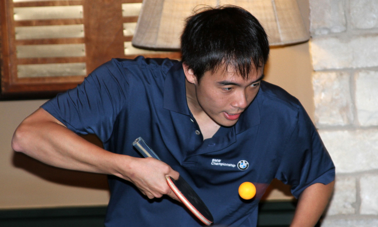 United States ping pong Olympian Timothy Wang serves a ball to Matt Kuchar during a friendly ping pong match in the players clubhouse while waiting out a rain delay during the pro am at Crooked Stck golf course in Carmel Indiana on Wed. Sept. 5, 2012 (Ian Yelton/WGA).