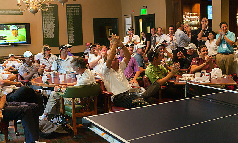 Golfers including Tiger Woods and Phil Mickelson cheer while Matt Kuchar plays United States ping pong Olympian Timothy Wang in the players clubhouse while waiting out a rain delay during the pro am at Crooked Stck golf course in Carmel Indiana on Wed. Sept. 5, 2012. (Charles Cherney/WGA)